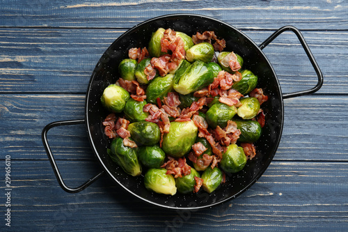 Fotografie, Obraz Tasty roasted Brussels sprouts with bacon on blue wooden table, top view