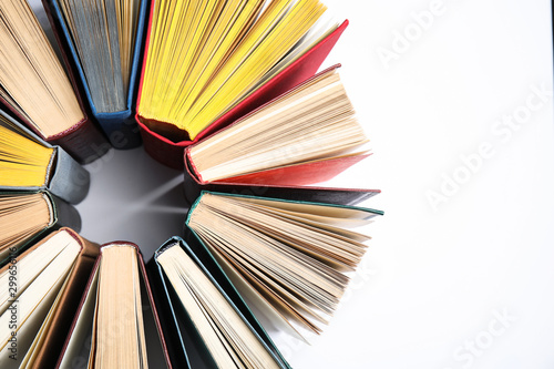 Circle made of hardcover books on white background, flat lay