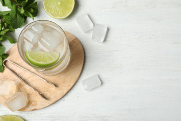 Flat lay composition of cocktail with vodka, ice and lime on white wooden table. Space for text