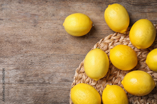 Fresh lemons on wooden table, flat lay. Space for text