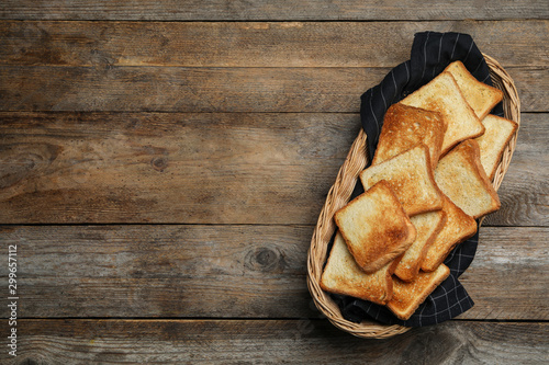 Fototapeta  Basket with toasted bread on wooden table, top view
