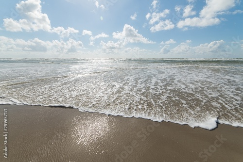 Fotografía  Beautiful shot of the ocean reaching its sandy shore and the bright calm sky in