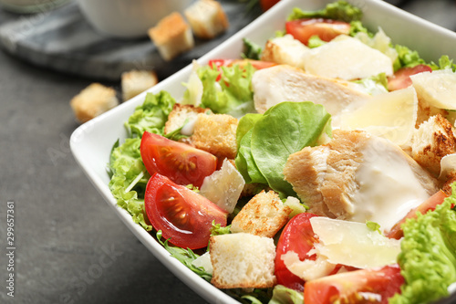 Fotomural  Delicious fresh Caesar salad in bowl on grey table, closeup