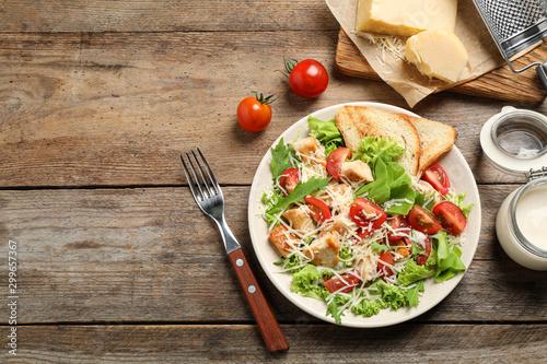 Fotobehang Kip Delicious fresh Caesar salad on wooden table, flat lay