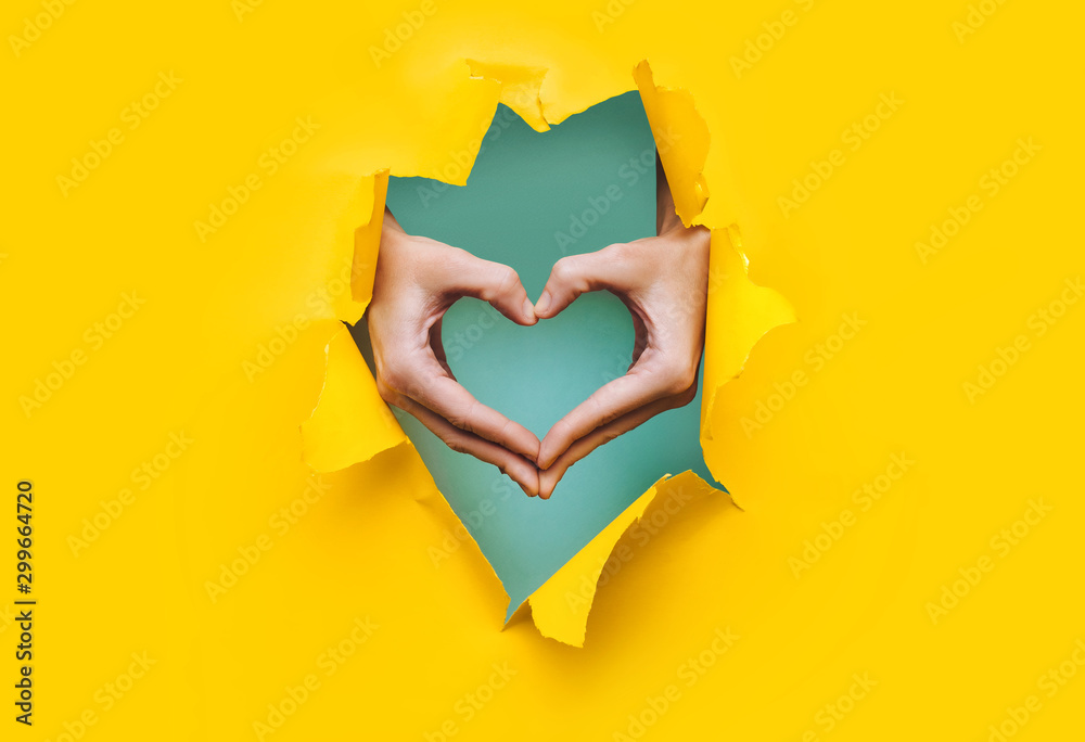 Fototapeta Female hands show a heart symbol through the torn holes of a yellow and green paper background. Creative art, copy space. Concept of love.