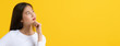 Cute asian young woman in white casual dress looking up and thinking / imagination isolated on yellow background in studio.banner size.
