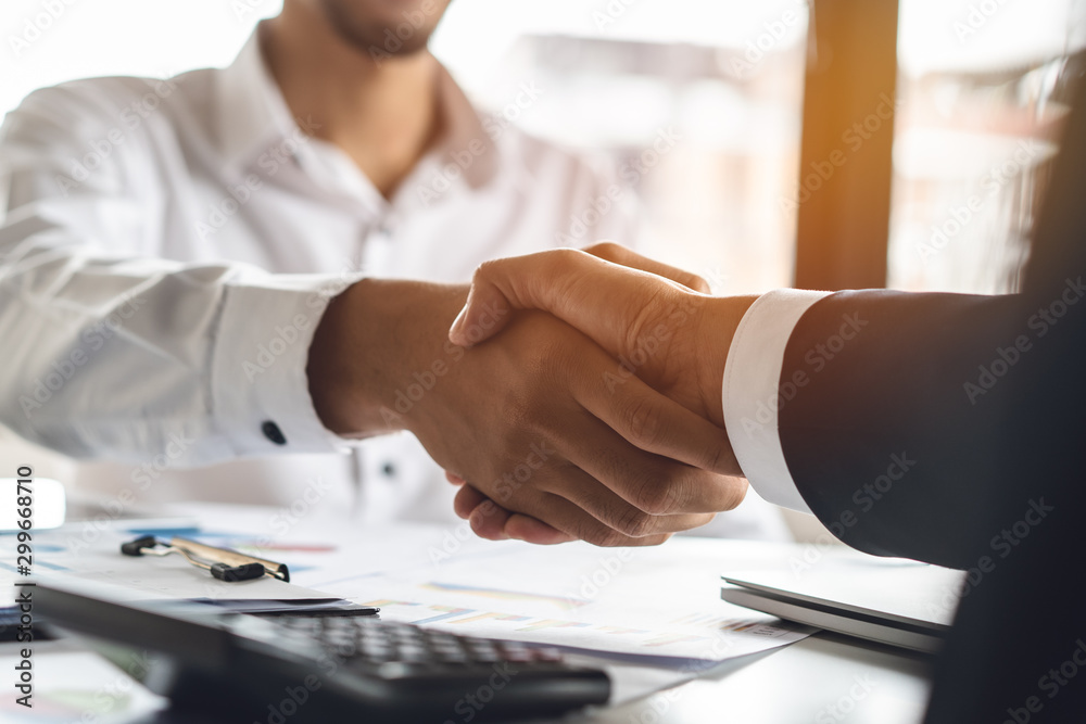 Fototapeta Banker and client shaking hands after business loan grant.