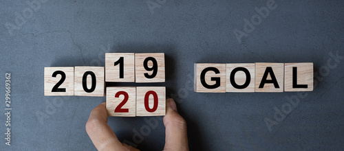Cuadros en Lienzo  Business man hand holding wooden cube with flip over block 2019 to 2020 GOAL word on table background
