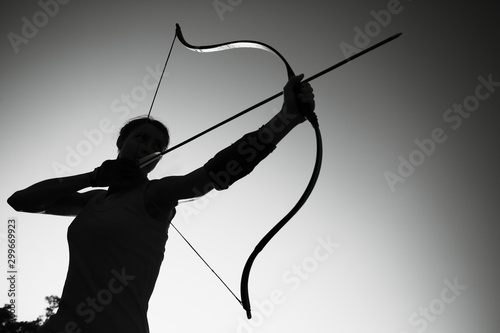 Young Caucasian female archer shooting with a bow in a field at sunset Wallpaper Mural