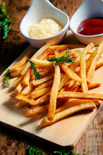 Crispy Fry Fries Placed On A Wooden Chopping Board With Two Dipping Sauces, Mayonnaise, Tomato Sauce