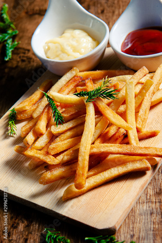 Obraz na plátne Crispy fry fries placed on a wooden chopping board with two dipping sauces, mayo