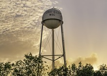 Water Tower In The Middle Of The Trees Under The Sunset
