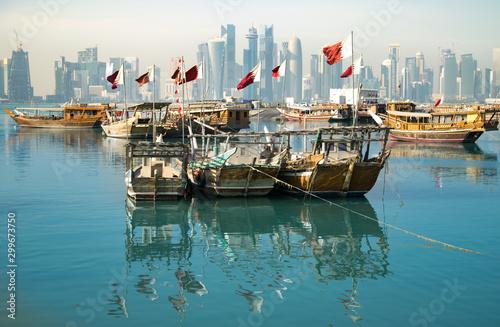 Fotografie, Obraz  Old wooden boats (dhows) with Qatari flags in Doha Harbor - Doha, Qatar