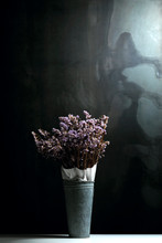 Statice Flowers In A Tin Vase With Black Metal Background. A High Contrast Style Of Photography