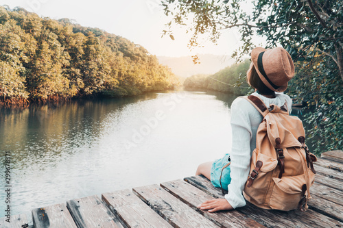 Obraz Cute girl backpacking and sitting on the wood plank resting and looking on the river. - fototapety do salonu