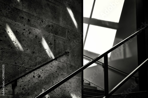 Grayscale shot of the railing of a staircase next to a stone wall - unknown future concept
