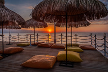 Straw Umbrellas And Pillows On...