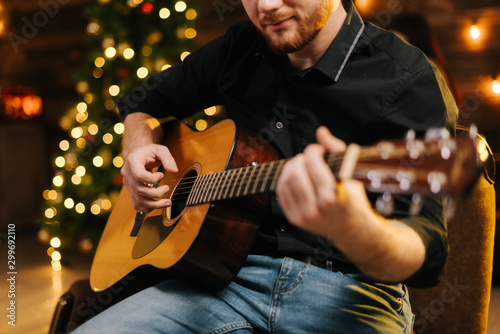 Happy young man is playing guitar. Guy is looking happily and carefree. Male in festive hat alone celebrating Christmas or new year. Christmas tree with garland in background. - 299692110