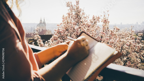 Fototapeta Girl enjoying sunny day in blooming garden on hill top over Prague. Cropped female hands writing in notepad or artist drawing sketch, camera focused at scenic city view and flowering magnolia tree. obraz