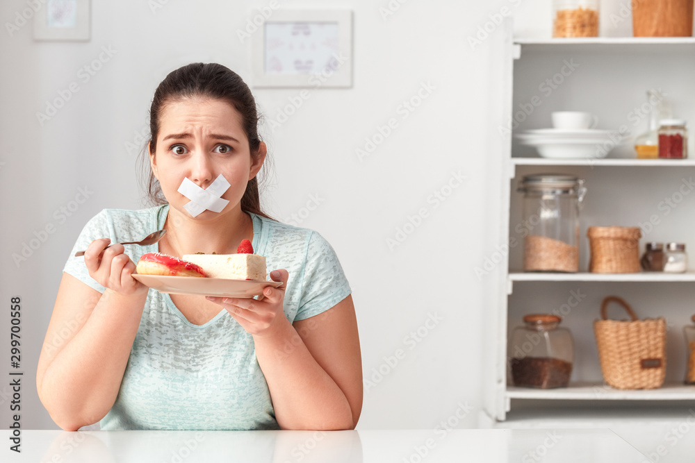 Fototapety, obrazy: Junk Food. Chubby girl taped with patch mouth sitting at kitchen table with desserts looking camera unhappy