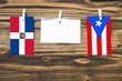 canvas print picture Hanging flags of Dominican Republic and Puerto Rico attached to rope with clothes pins with copy space on white note paper on wooden background.Diplomatic relations between countries.