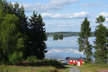 Finnish Beach With Bathouse And Scenery At A Lake