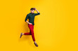Turned ful llength body size photo of serious fashionable man with hand in red pants pocket running for sales towards barbershop for cheap service isolated vibrant color background