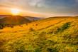 Leinwandbild Motiv Landscape sunset in mountains with forest, green grass and big shining sun on dramatic sky