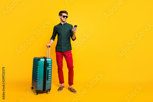 Fototapeta Full size profile side photo of cheerful traveler guy on summer vacation reach destination hold package use cellphone reserve taxi wear green shirt pants trousers isolated yellow color background obraz
