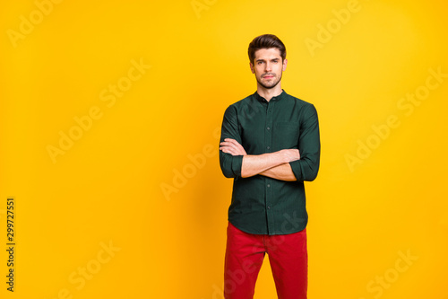 Photo of serious attractive confident man standing with arms crossed wearing red trousers watching his employees pass final test to get job isolated over yellow bright color background