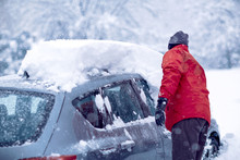 Car Stuck In Snow. Man Brushing The Snow Off His Car On A  Winter Day