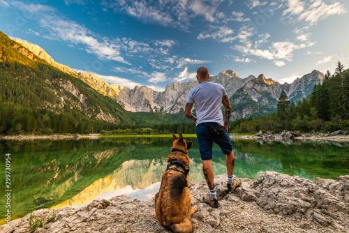 fototapeta na ścianę Adventure Man Standing With Dog at Beautiful Lake, Fusine Lake , Italy