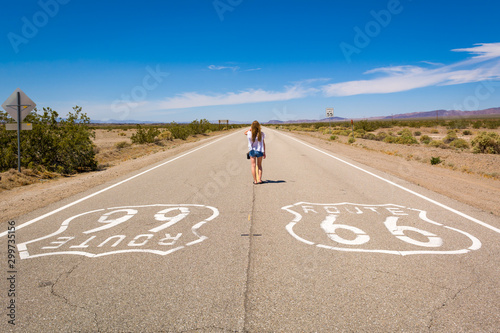 Photo Young woman standing on the Route 66 road in Californian desert