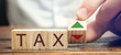 Leinwandbild Motiv Wooden blocks with the word Tax and up and down arrows. Business and finance concept. Taxes and taxation. The tax burden