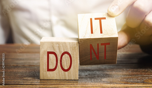 Obraz Businessman puts wooden blocks with the words Do it and don't. The concept of motivation and self-development. Goal achievement. - fototapety do salonu