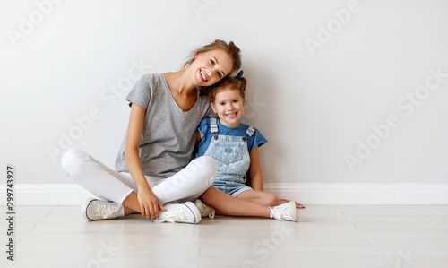Obraz happy family mother (big sister) and child daughter near an empty wall. - fototapety do salonu