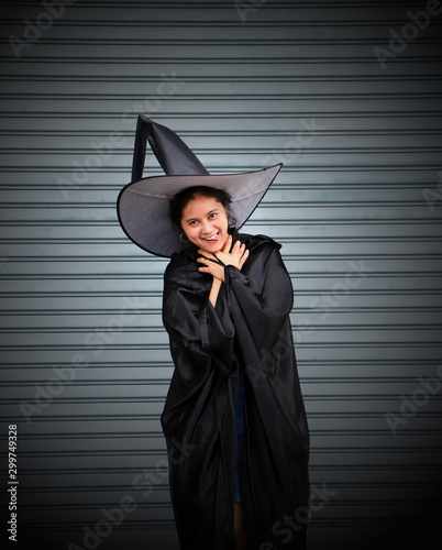 Woman with black cape and witch hat use her hands to strangle her neck on stripe metal background Tablou Canvas