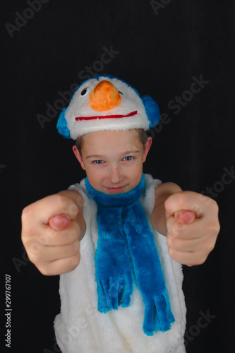 Photo A child in a snowman costume smiles and shows a nevermind on a black background