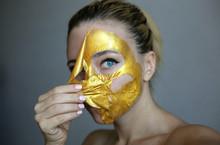 Beautiful Girl Peeling Off Golden Face Mask. Skin Treatment.
