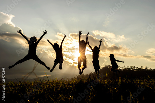 Silhouette group of happy children jumping playing on mountain at sunset, summer time