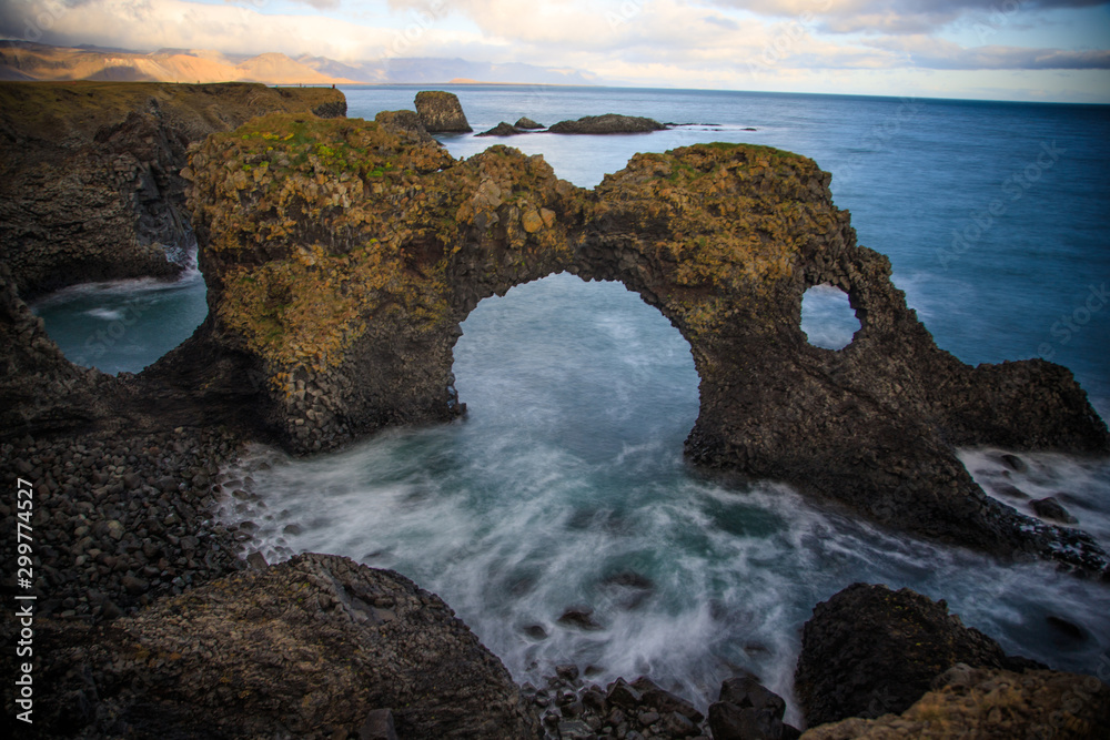 Fototapeta West coast sea cliffs of Snaefellsnes Peninsula on Iceland in long exposure photo. Pure blue water with high cliffs above sea. Beautiful colourful scenic view of basalt rock reef..