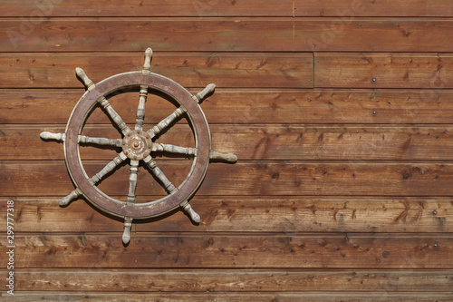Wall Murals Ship Old ship steering wheel hangs on the wooden wall