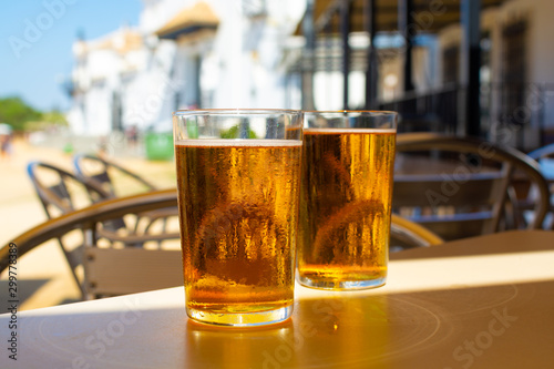 Foto auf Leinwand Alkohol Cold amber color light spanish beer served in glass in outdoor cafe in town on sand, El Rocio in Andalusia, Spain