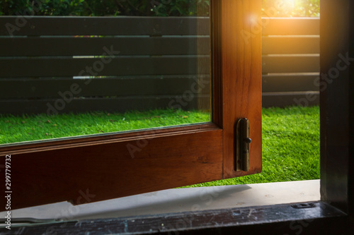 Low angle ajar door made from clear mirror and wooden frame with radiant sunlight Canvas Print