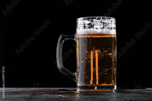 Fotografia  Glass mug filled with fresh beer with foam against black background