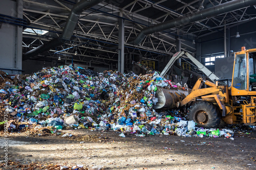 Photo  excavator stacks trash in big pile at sorting modern waste recycling processing plant