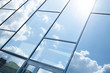 Glass building facade with blue sky reflection