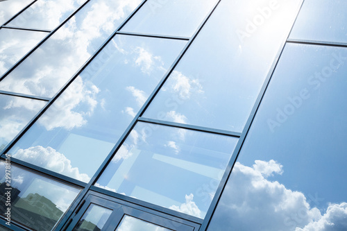 Photo Glass building facade with blue sky reflection