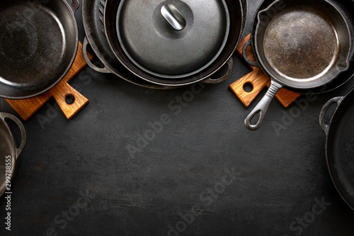 Fototapeta Kitchen utensils dark background with cast iron black kitchenware obraz