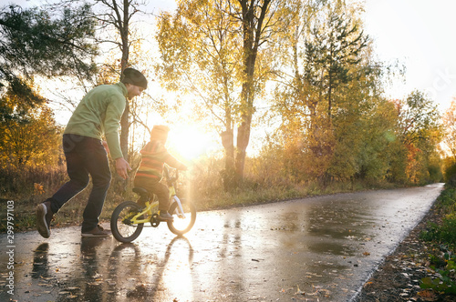 Photo Father teaches his little child to ride bike in autumn park